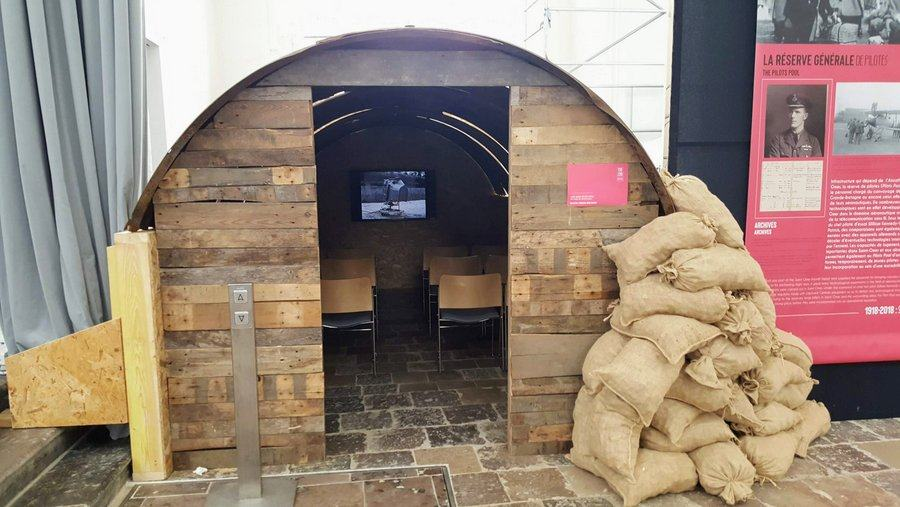 The entrance of a sandbagged hut. Inside can be seen rows of chairs and a video display