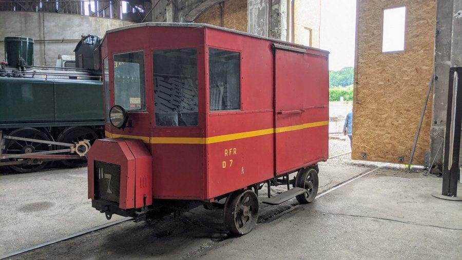 A small square red vehicle that looks more like a Post Office van than a locomotive
