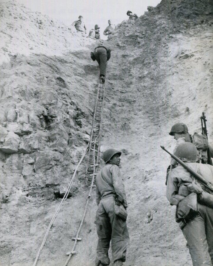 B&W photo of Rangers climbing up the cliff