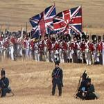 Colourful red-tunic 19th century soldiers with huge Union flags formed up in a dusty brown cornfield