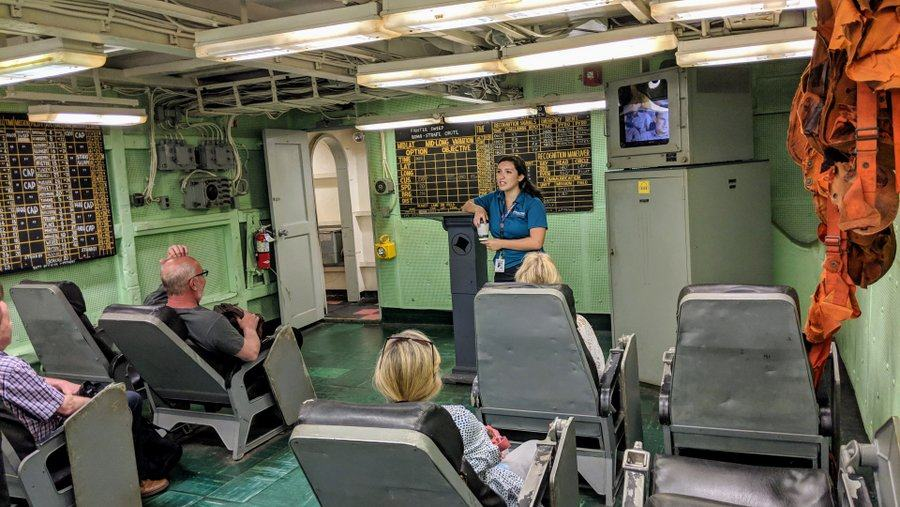 A squadron briefing room with rows of comfy seats in theatre style