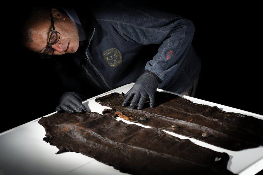 An investigator examines parts of a leather tunic on a light table