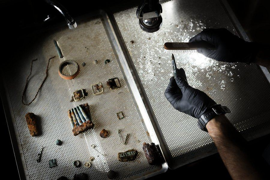Small items such as rings, buttons, a clip of bullets are being closely cleaned and examined