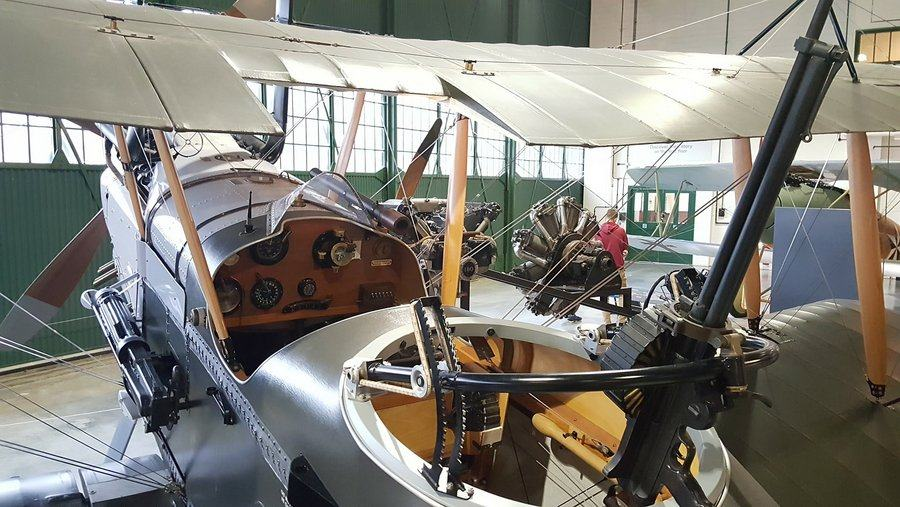View into the cockpit of the British RE8 biplane with its rudimentary instruments on a wooden dashboard.