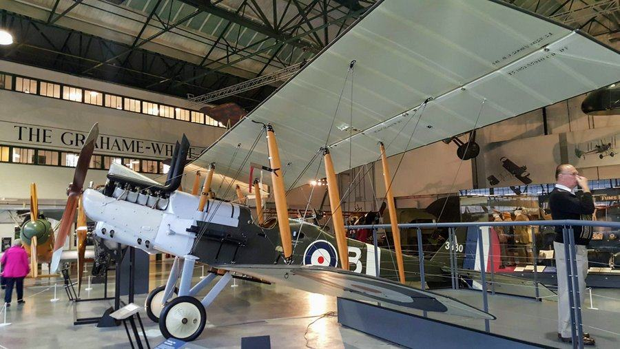 Large British biplane with a pair of exhaust 'chimneys' ... and standing nearby, rather bizarrely, a man blowing his nose!b