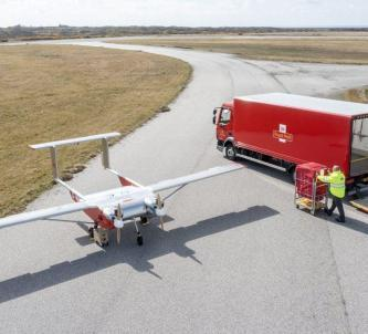 A Royal Mail UAV and parcel truck meet on the airfield