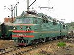 Green & red painted Russian electric loco in dusty Murmansk rail yard