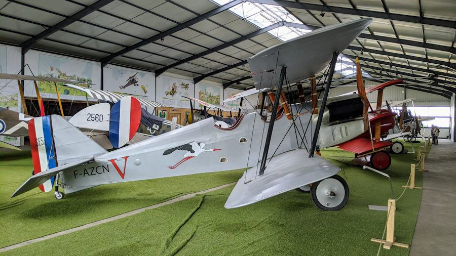 Grey-painted biplane with flying stork emblem. This replica SE5 is on display at the Salis Flying Museum