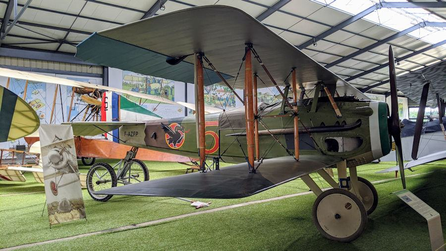Green painted WWI biplane with a tricolour on the rudder, On displayin a hanger at the Salis Flying Museum.