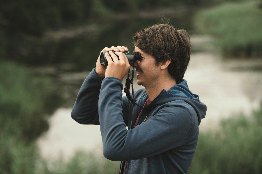 A man looking through an optical device that looks like a pair of binoculars