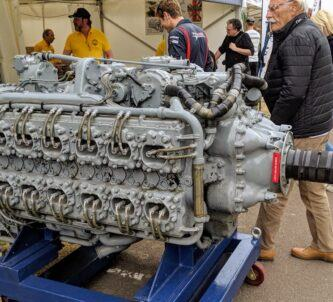 A large, grey painted, aero engine on a stand outside a showground tent. People are milling about.
