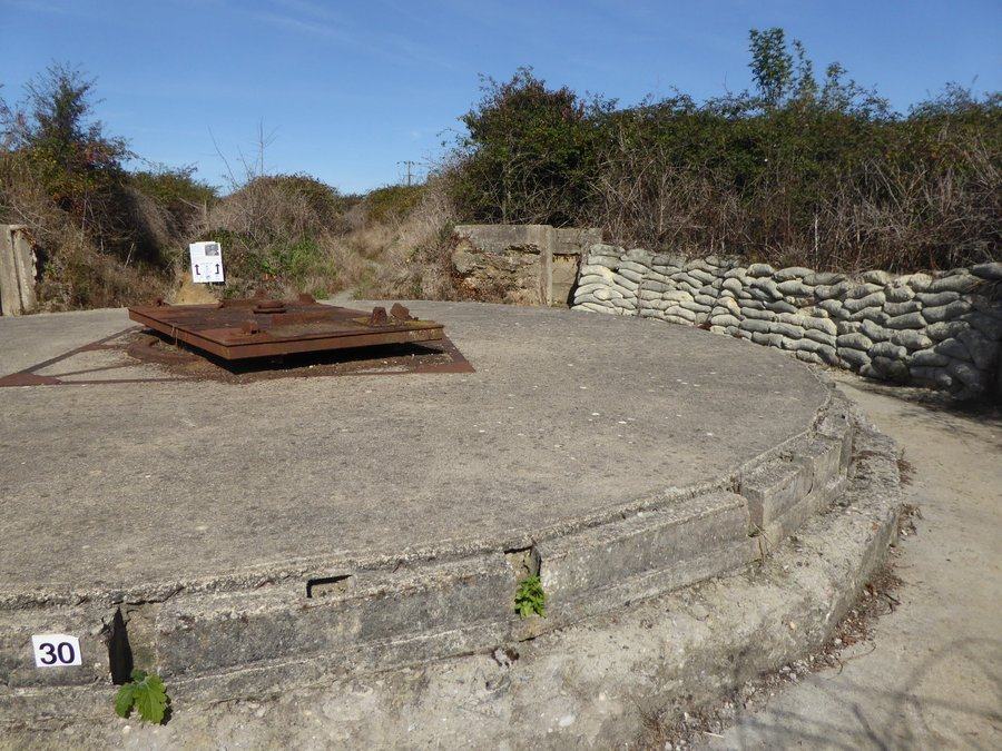 A large circular concrete gun emplacement with a rusty plinth in the centre