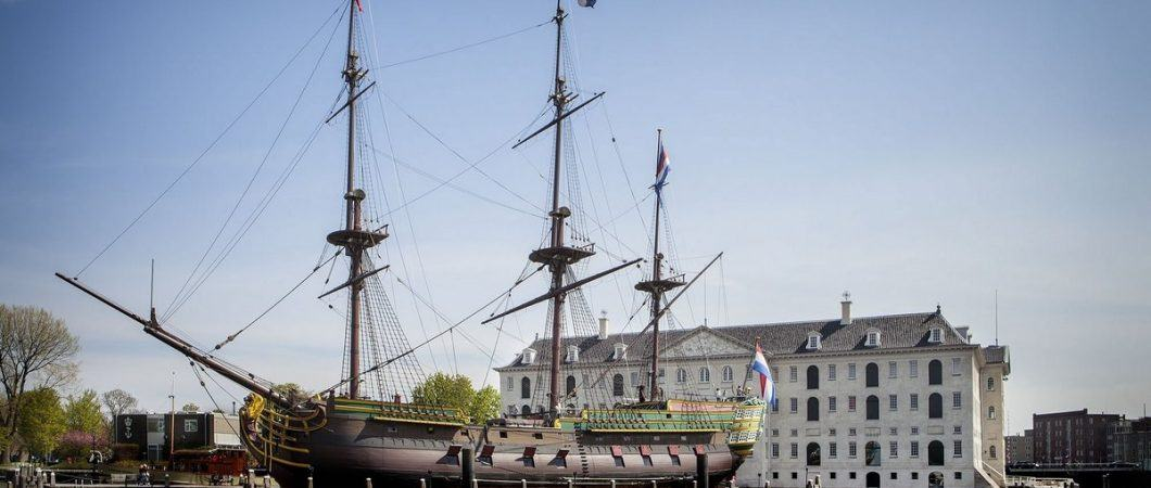 A three masted frigate flying the Dutch flag at her stern is moored in front of the grand classical building of the National Maritime Museum