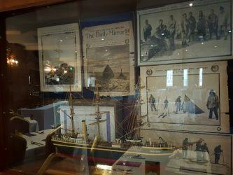 A glass display case with newspapers and ma ship model from 1910