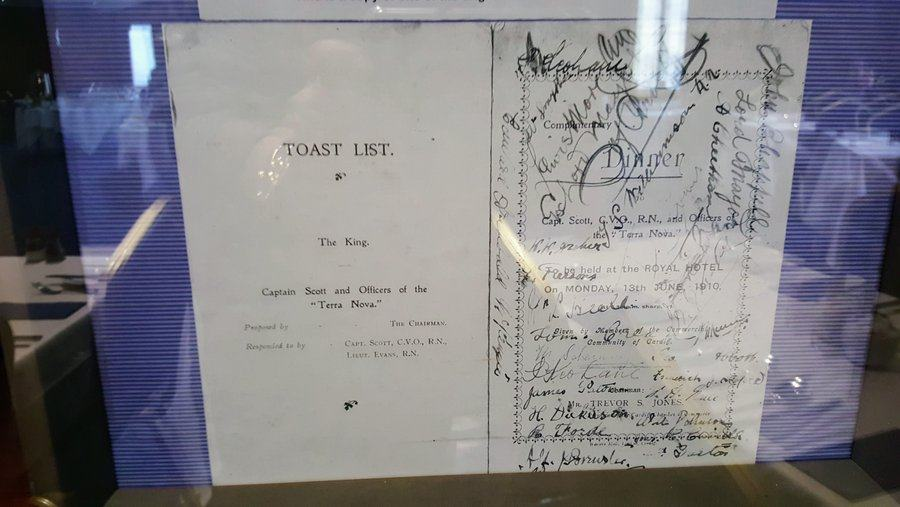 A list of formal toasts with signatures scrawled all over it, behind reflective glass