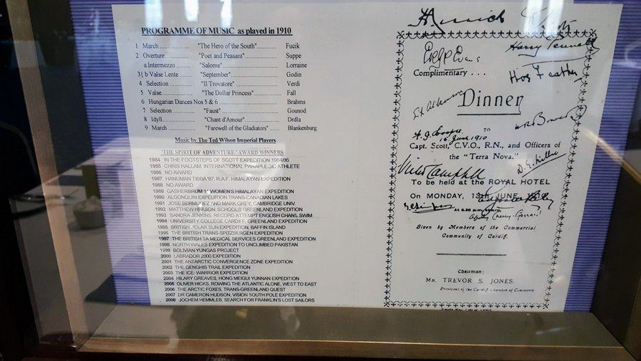 A printed menu with signatures scrawled on it, displayed behind reflective glass