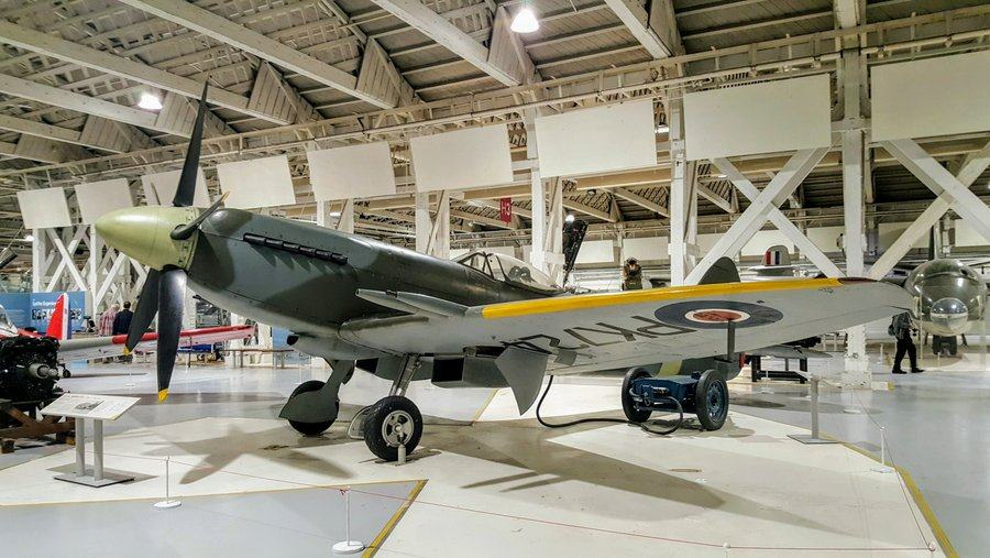 Grey & green camouflaged Spitfire with 5-bladed propeller and large canons emerging from yellow leading edges of the wings.