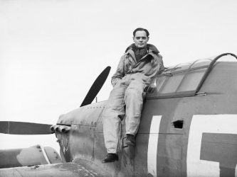 SL Douglas Bader sat on his Hurricane fighter aircraft