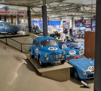 Post-war race cars on display, mostly painted blue