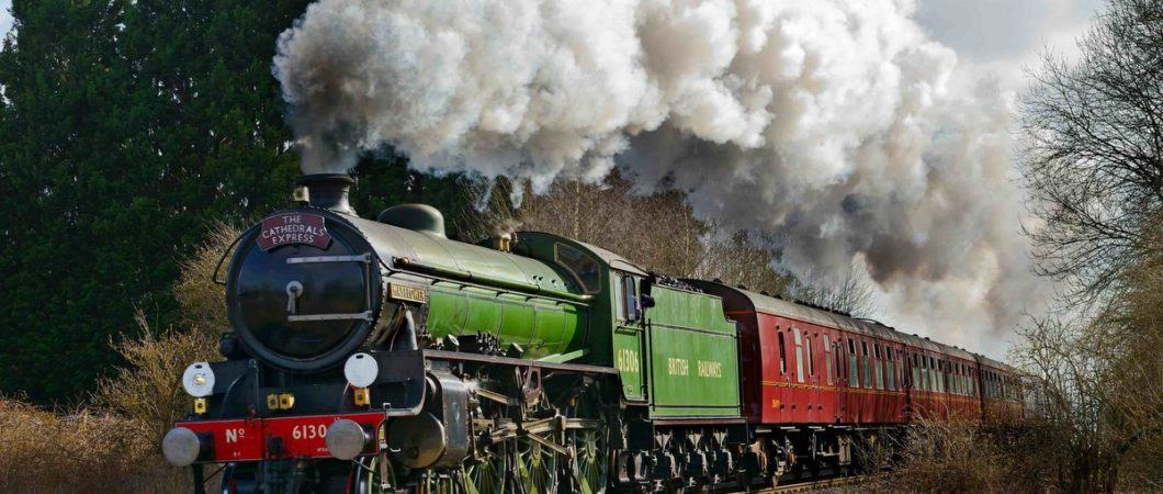 A green steam locomotive hauls classic red pullman carriages through a woodland cutting. There's much smoke and steam.