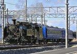 Steam loco surrounded by electric railway line pylons and tracks
