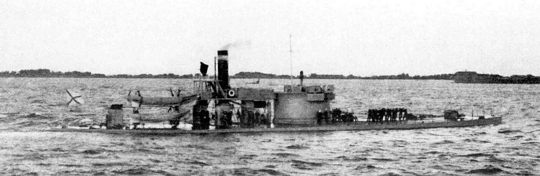 Grainy B/W image of an armoured gunboat, very low in the water (looking rather more like a submarine) with superstructure, a tall funnel, and a large gun turret