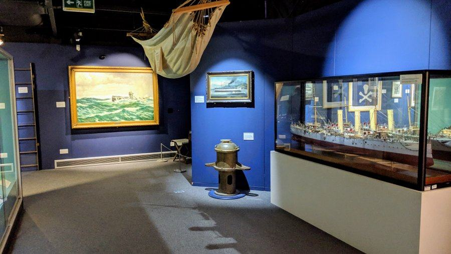 Museum gallery with blue walls, paintings, display cases and artifacts including a hammock slung from the ceiling