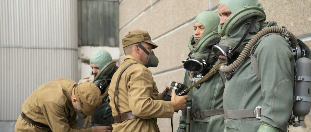 Three men in heavy green suits with masks and breathing apparatus are stood against a wall while two soldiers help to prepare them.