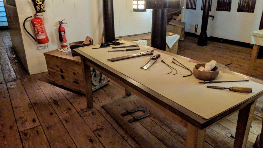 A table with medical saws, pincers and probs laid out on it.
