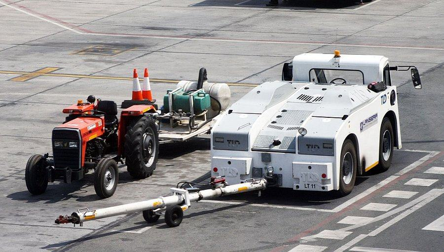A large white aircraft tractor sits on the tarmac