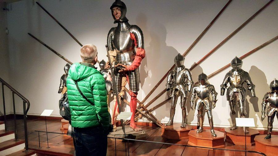 A visitor looks up at the armoured mannequin of Bartelmä Bon surrounded by suits of armor for children
