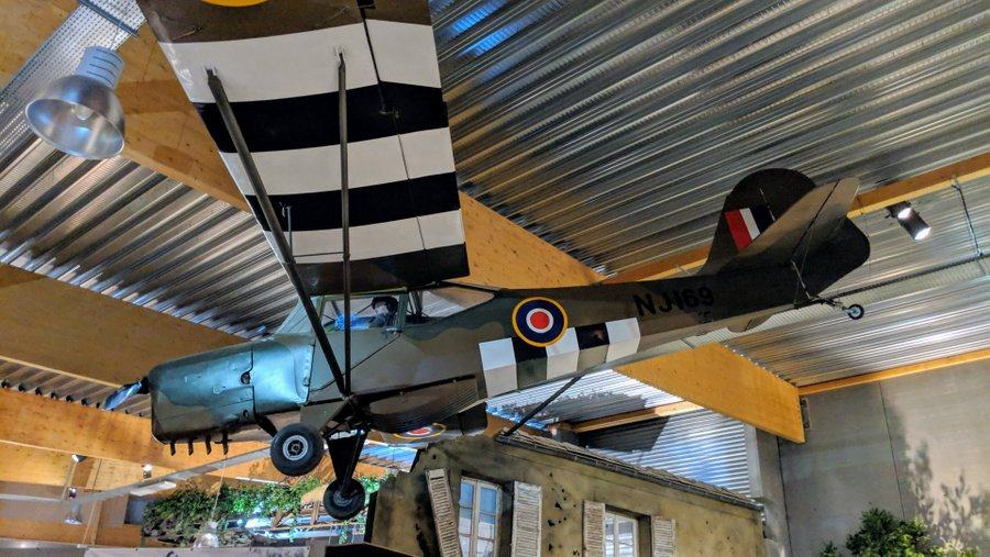 Light passenger aircraft suspended in the museum ceiling. It is camouflaged in brown & green and has black & white 'invasion stripes' painted on the wings