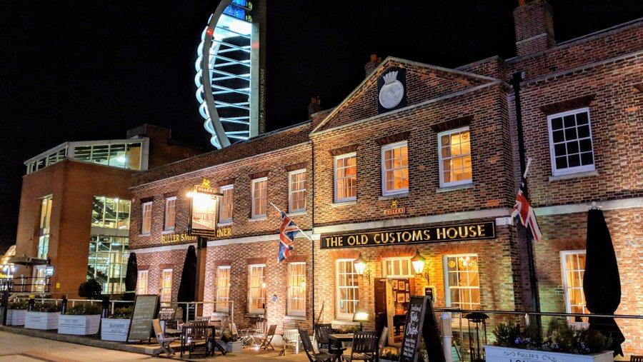 Night shot of an old brick building with facade lit up and the Spinnaker Tower above