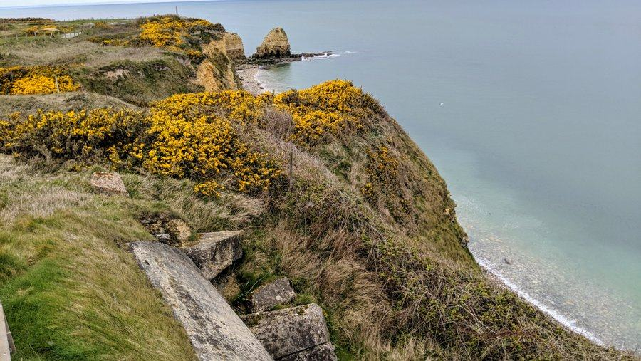 A view along the cliff with grass and yellow gorse, down to the beach and a promontory in the distance