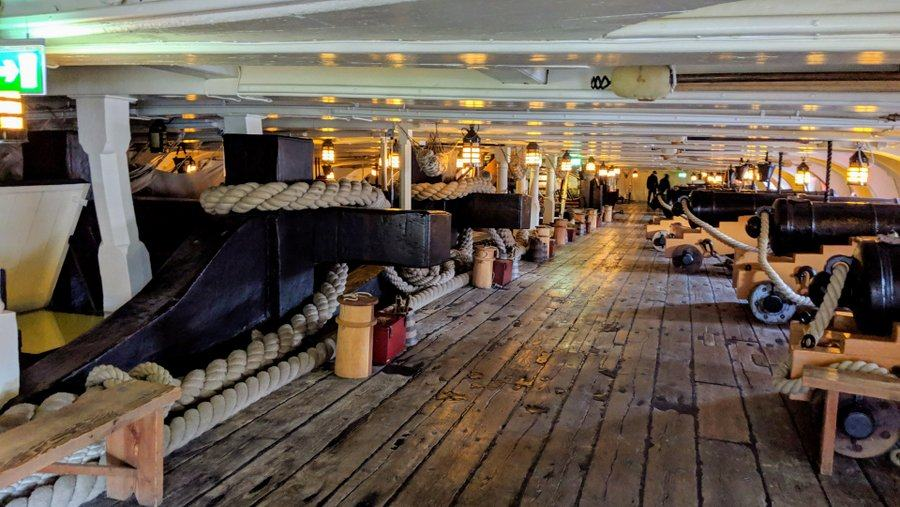 Looking down the lower gun deck, the anchor rope is coiled around railway-sleeper sized black timber stubs