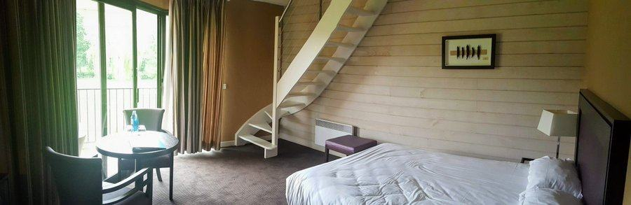 Wide angle shot of a hotel room with a staircase leading upstairs