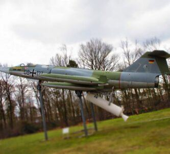 Green and grey pencil-thin German Starfighter with a white JATO rocket underneath, mounted on a display stand outside with grass & tress behind