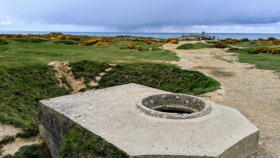 A flat topped concrete bunker amon the green grassed craters, with a hole in the top for a machine gunner