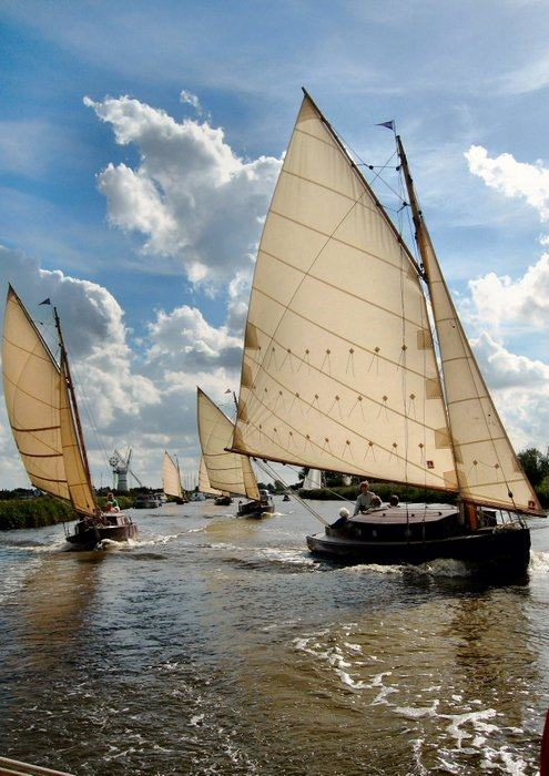 Traditional sailboats sail along a channel in the Norfolk Broads