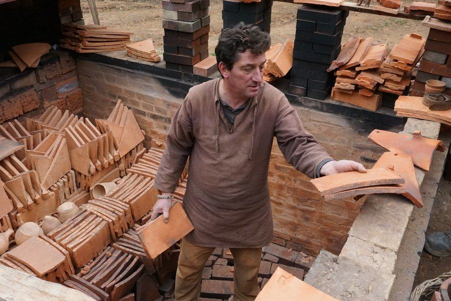 A man stand among stacks of terracotta red tiles