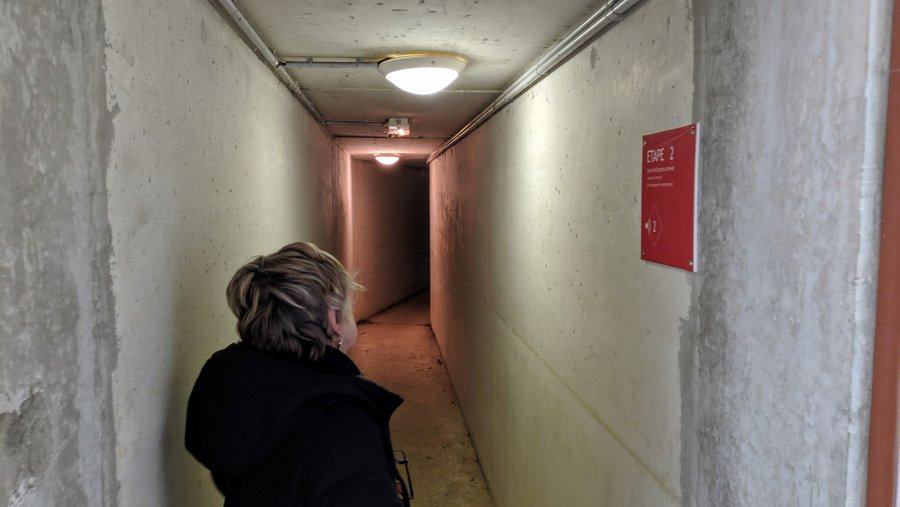 A woman looks at a sign in a narrow tunnel