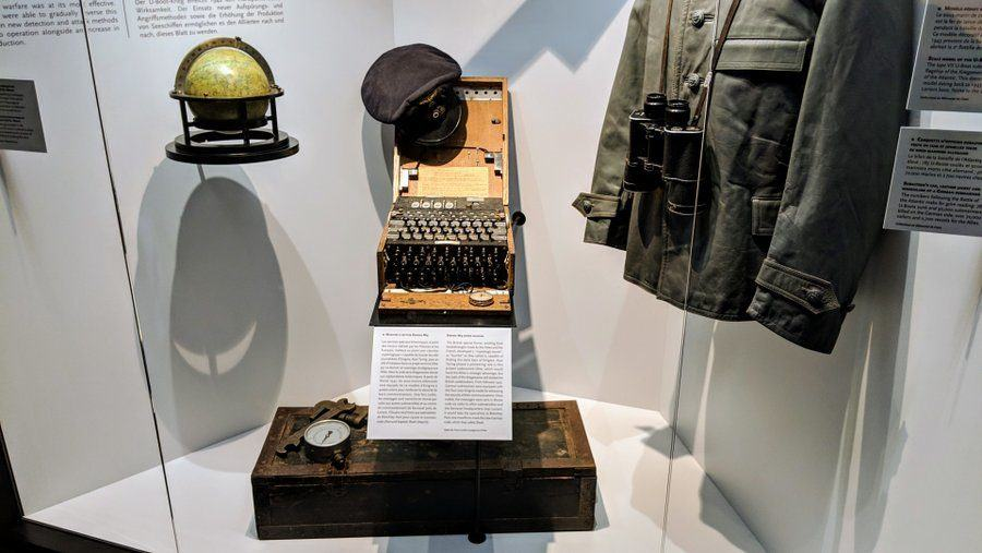Display case with U-boat artifacts including a waterproof jacket and an Enigma coding machine