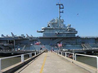 Aircraft carrier moored alongside under a clear blue sky