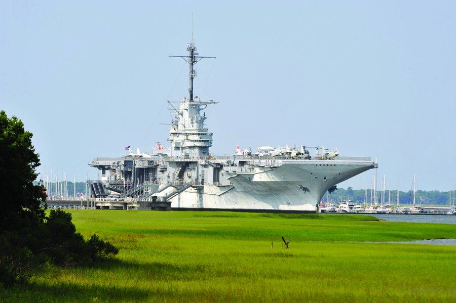A grey aircraft carrier across a bright green floodplain