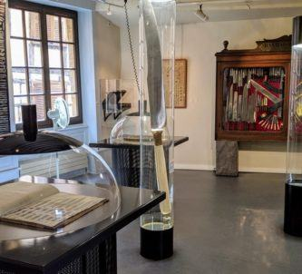 Museum gallery with items, mostly knives, in domed glass cases and on the walls