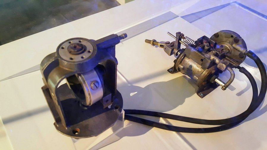 Two metal devices in a cabinet looking rather like a motor car distributor or carburettor or