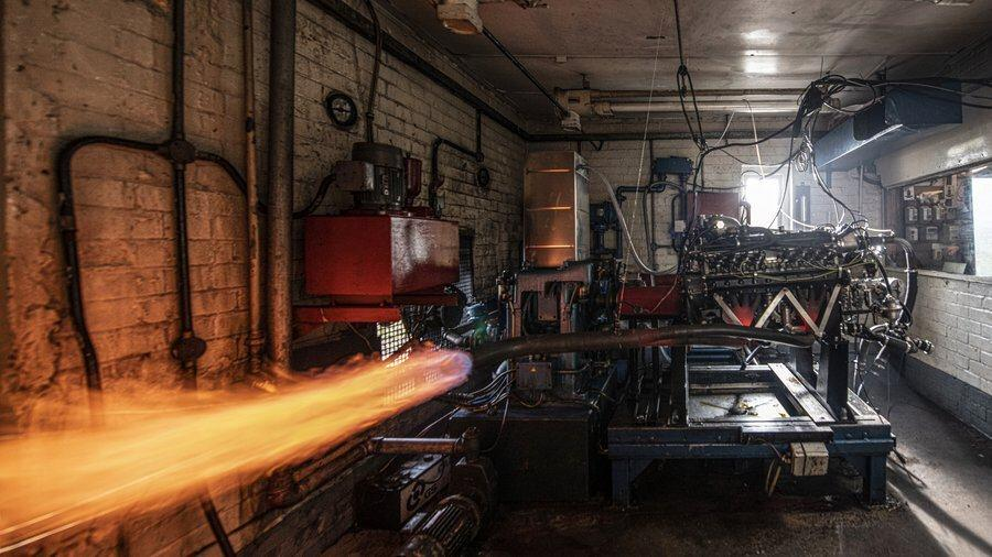 Flames belch from the BRM V16 engine exhaust in a motor workshop