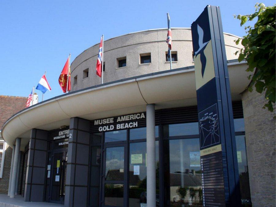 Front of the Musée America Gold Beach with glass doors and a row of flags on top. Sunny day.