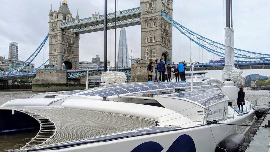 People on the deck of the catamaran with Tower Bridge behind
