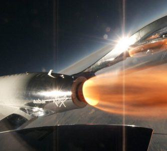 Spaceship with rocket burning on the edge of space